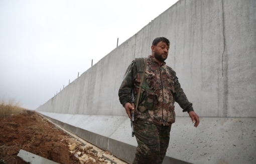 A Kurdish People's Protection Unit (YPG) fighter walks near a wall which activists say was put up by Turkish authorities, on the Syria-Turkey border in the western Syrian countryside of Ras al-Ain on February 2, 2016. / AFP PHOTO / DELIL SOULEIMAN